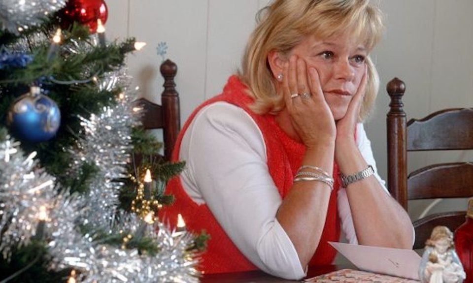 Woman looking fed up, with head in hands beside Christmas tree
