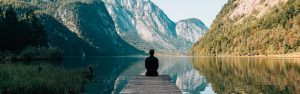 Man relaxing on a jetty looking out on a beautiful lake surrounded by majestic mountains