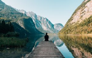 Sitting on a wooden dock looking out over calm lake surrounded by mountains