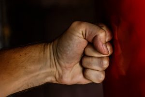 Clenched fist punching a wall in anger